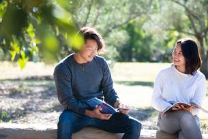 緑の中で座って話している男女二人の写真素材 [FYI02987148]
