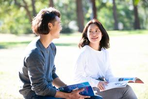 芝生に座って勉強をしている男女二人の写真素材 [FYI02987202]