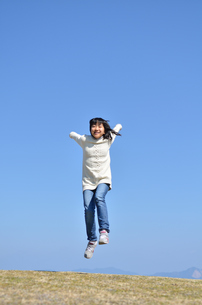 青空でジャンプする女の子(芝生広場)の写真素材 [FYI02987205]