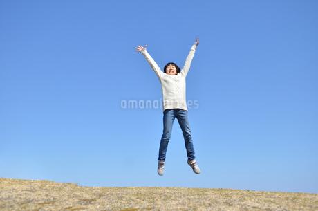 青空でジャンプする女の子(芝生広場)の写真素材 [FYI02987210]