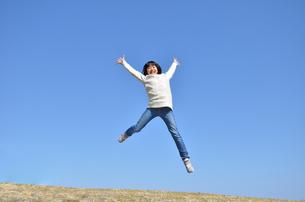 青空でジャンプする女の子(芝生広場)の写真素材 [FYI02987211]