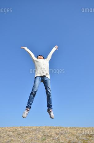 青空でジャンプする女の子(芝生広場)の写真素材 [FYI02987215]