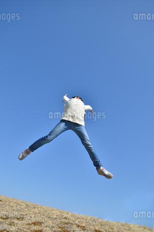 青空でジャンプする女の子(芝生広場)の写真素材 [FYI02987220]