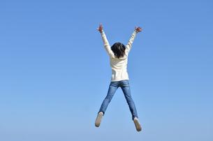 青空でジャンプする女の子(後姿)の写真素材 [FYI02987224]