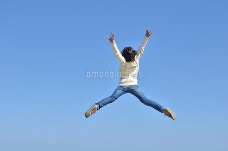 青空でジャンプする女の子(後姿)の写真素材 [FYI02987225]