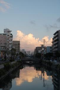川にビルと雲が反射する都会の写真素材 [FYI02987594]