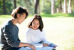 芝生に座って本を見ている男女二人の写真素材 [FYI02987784]