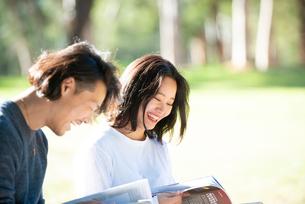 芝生に座って本を見ている男女二人の写真素材 [FYI02987790]