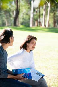 芝生に座って本を開いて笑っている男女の写真素材 [FYI02987800]