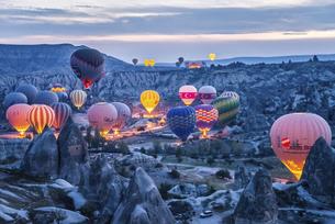 夜明け前奇岩群のなか飛行準備をする沢山の熱気球の写真素材 [FYI02988410]