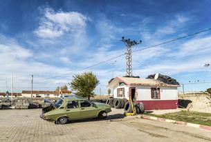 タイヤ修理中の車を見るトルコ田舎のドライブイン風景の写真素材 [FYI02988428]