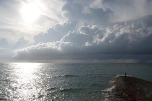 入道雲が迫る海と堤防の釣り人の写真素材 [FYI02988461]