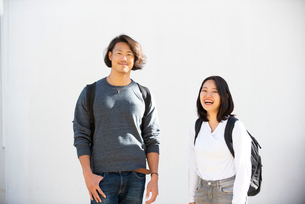 白い壁の前に立っている男女の写真素材 [FYI02988953]