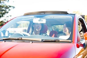 赤い車でドライブしている男女の写真素材 [FYI02988966]
