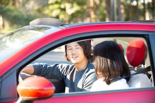 赤い車でドライブしている男女の写真素材 [FYI02988967]