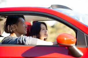 赤い車でドライブしている男女の写真素材 [FYI02989233]