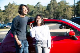 赤い車の前で笑っている男女の写真素材 [FYI02989234]