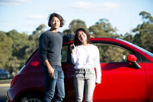 赤い車の前に立っている男女の写真素材 [FYI02989269]