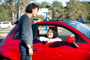 赤い車の前で話している男女の写真素材 [FYI02989270]
