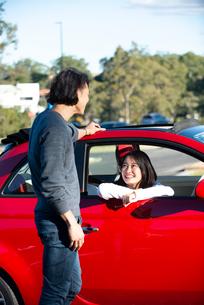 赤い車の前で話している男女の写真素材 [FYI02989272]