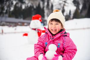 雪山で雪だるまを持つ子供の写真素材 [FYI02989451]