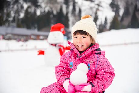 雪山で雪だるまを持つ子供の写真素材 [FYI02989465]