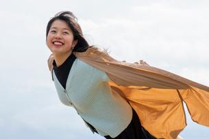 コートが風でふくらみ空を飛ぶ感じと喜ぶ女性の写真素材 [FYI02989482]