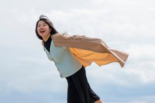 コートが風でふくらみ空を飛ぶ感じと喜ぶ女性の写真素材 [FYI02989483]