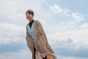 大空の下コートに両手を入れて笑う女性の写真素材 [FYI02989486]