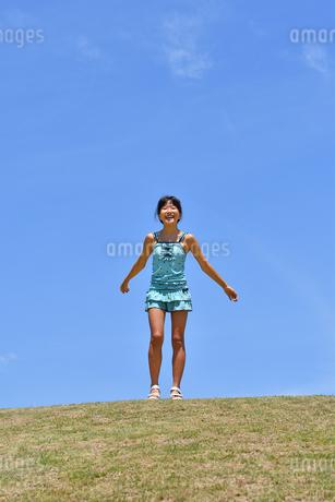 青空で笑う女の子(海水浴、水着、芝生広場)の写真素材 [FYI02990457]