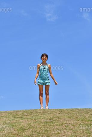 青空で笑う女の子(海水浴、水着、芝生広場)の写真素材 [FYI02990458]