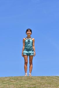 青空で笑う女の子(海水浴、水着、芝生広場)の写真素材 [FYI02990459]