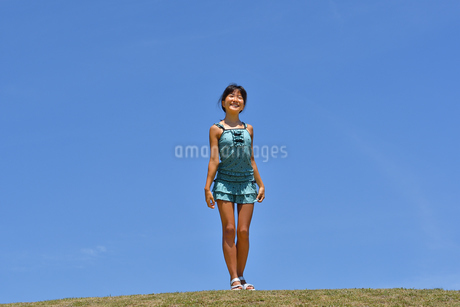 青空で笑う女の子(海水浴、水着、芝生広場)の写真素材 [FYI02990460]