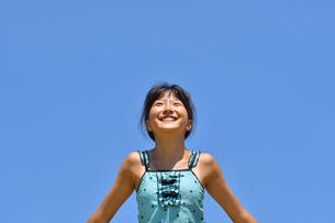 青空で笑う女の子(海水浴、水着)の写真素材 [FYI02990461]