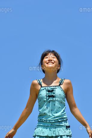 青空で笑う女の子(海水浴、水着)の写真素材 [FYI02990462]