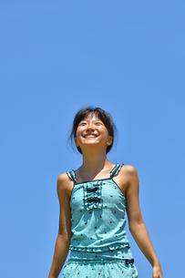 青空で笑う女の子(海水浴、水着)の写真素材 [FYI02990463]