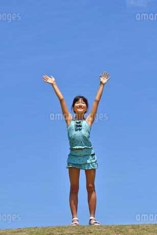 青空でバンザイする女の子(海水浴、水着、芝生広場)の写真素材 [FYI02990464]