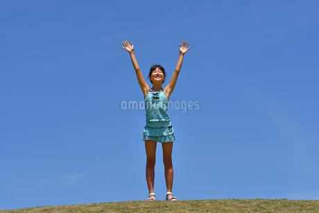 青空でバンザイする女の子(海水浴、水着、芝生広場)の写真素材 [FYI02990466]