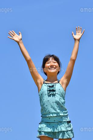 青空でバンザイする女の子(海水浴、水着)の写真素材 [FYI02990468]