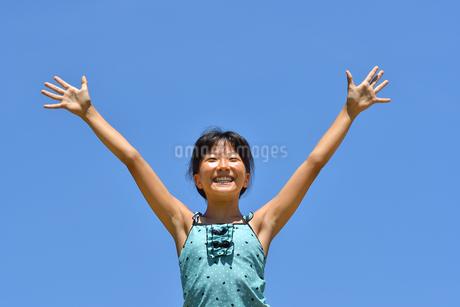 青空でバンザイする女の子(海水浴、水着)の写真素材 [FYI02990470]