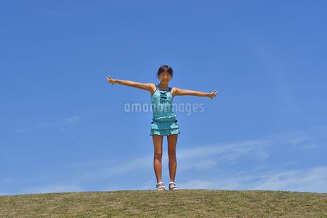 青空で笑う女の子(海水浴、水着、芝生広場)の写真素材 [FYI02990472]