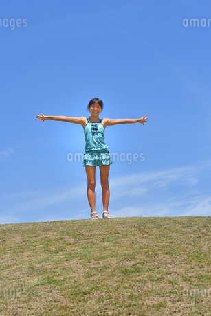 青空で笑う女の子(海水浴、水着、芝生広場)の写真素材 [FYI02990474]