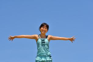 青空で笑う女の子(海水浴、水着)の写真素材 [FYI02990475]