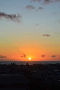 水平線に沈む夕日と都会のシルエットの写真素材 [FYI02990496]