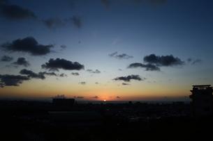 水平線に沈む夕日と都会のシルエットの写真素材 [FYI02990508]