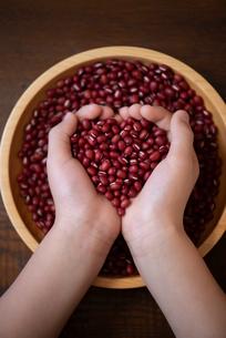 両手いっぱいに小豆を持った子どもの手の写真素材 [FYI02990945]