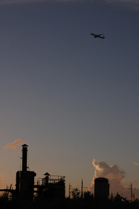 快晴の夕暮れに飛行する航空機と小さな工場の写真素材 [FYI02991096]