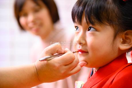 口紅をつけてもらう晴れ着の女の子の写真素材 [FYI02991498]