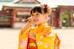 糸電話で遊ぶ晴れ着の女の子の写真素材 [FYI02991557]