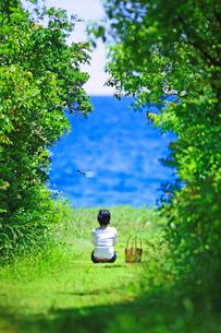 海へと続く野道に座り海を眺める女性の写真素材 [FYI02992510]